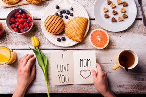Mothers day composition. Hands of unrecognizable woman holding greeting card with I love you, Mom, text. Breakfast meal. Studio shot on wooden background.