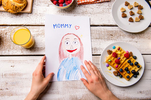 Mothers day composition. Hands of unrecognizable woman holding her childs drawing of her, breakfast waffles with fruit. Studio shot on wooden background.