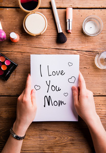 Mothers day composition. Hands of unrecognizable woman holding I love you Mom note. Various beauty products laid on table. Studio shot on wooden background. Flat lay