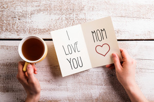 Mothers day composition. Hands of unrecognizable woman holding note with I love you mom text and cup of tea. Studio shot on white wooden background. Flat lay.