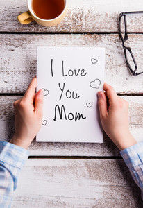 Mothers day composition. Hands of unrecognizable woman holding note with I love you mom text. Cup of tea and eyeglasses. Studio shot on white wooden background. Flat lay.