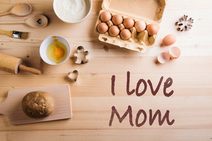 Mothers day composition. I love mom sign. Baking ingredients and kitchen utensils. Wooden backround. Studio shot.