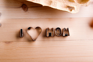 Mothers day composition. I love mom sign made of cookie cutters. Studio shot on wooden background.