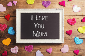 Mothers day composition. I love you sign in picture frame. Colorful fabric hearts. Studio shot on wooden background.
