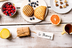 Mothers day composition. Little gift with For Mommy tag. Breakfast meal. Studio shot on wooden background.