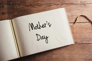 Mothers day composition. Photo album, book. Studio shot on wooden background.