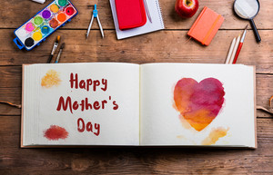 Mothers day composition. Photo album with watercolor heart and Happy Mothers Day sign, school supplies. Studio shot on wooden background.