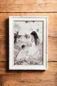 Mothers day composition. Photo of mother and daughter in picture frame. Studio shot on wooden background.
