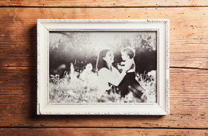 Mothers day composition. Photo of mother and son in picture frame. Studio shot on wooden background.
