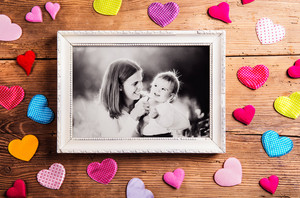 Mothers day composition.  Photo of mother with her son in picture frame. Colorful fabric hearts. Studio shot on wooden background.