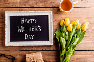 Mothers day composition. Picture frame with chalk sign, bouquet of yellow tulips, gift and cup of tea. Studio shot on wooden background.