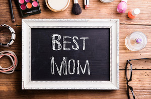 Mothers day composition. White picture frame with black board in it and chalk Best mom sign. Various beauty products laid on table. Studio shot on wooden background. Flat lay.