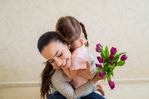 Mothers day, cute little girl giving violet tulips to her mother, hugging her