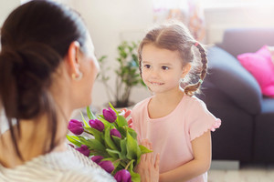Mothers day, cute little girl giving violet tulips to her mother