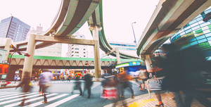Motion blurred crowds crossing a busy intersection in Ikebukuro, Tokyo, Japan