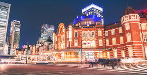 Motion blurred people crossing the intersection in front of Tokyo station at night