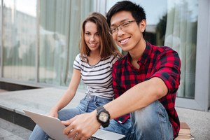 Multiethnic cheerful young couple talking and using laptop together outdoors