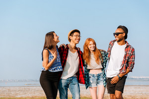 Multiethnic group of cheerful young friends standing together and laughing outdoors