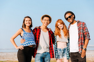 Multiethnic group of happy young friends standing outdoors together