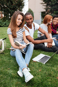 Multiethnic group of happy young people reading book and using laptop on lawn outdoors