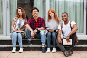 Multiethnic group of happy young people sitting in campus together