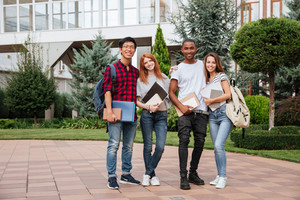 Multiethnic group of happy young people standing in campus together outdoors
