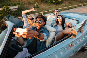 Multiethnic group of joyful young friends taking selfie with mobile phone in cabriolet