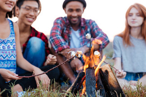 Multiethnic group of of cheerful young people talking and preparing marshmallows on bonfire outdoors in summer
