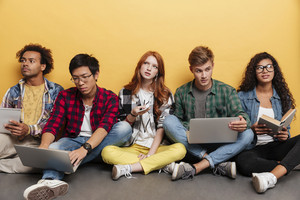 Multiethnic group of serious young people with laptops sitting and learning over yellow background