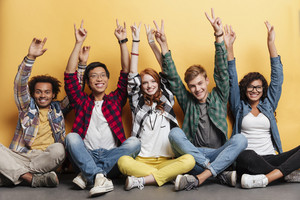 Multiethnic group of smiling young people sitting and celebrating success with raised hands