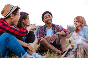Multiethnic group of smiling young people sitting and talking near campfire