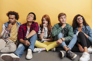Multiethnic group of thoughtful young friends sitting and thinking