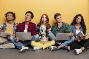 Multiethnic group of thoughtful young people with laptops sitting and thinking over yellow background