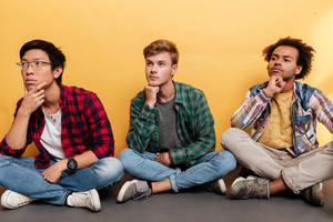 Multiethnic group of three pensive young men friends thinking and looking away over yellow background