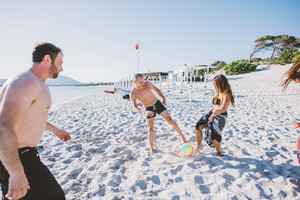 Multiethnic group outdoor playing soccer on the beach - sportive, summer time, having fun concept