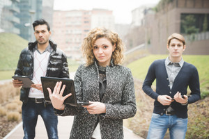 Multiracial business people posing outdoor in town holding technological devices like tablet, smartphone and computer - focus on the businesswoman lookin in camera - team, businees, work concept