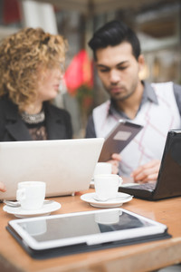 Multiracial business people working connected with technological devices in a bar, focus on devices and cup of coffee - technology, business, communication concept