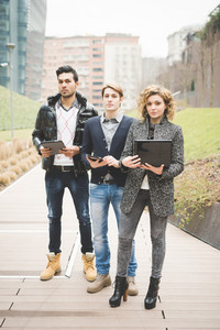 Multiracial contemporary business people posing outdoor with technological devices like notebook and tablet on their hands, looking in camera - business, finance, technology concept