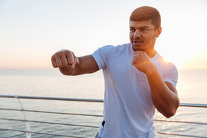 Muscular african american young man athlete standing and practicing martial arts on sunrise
