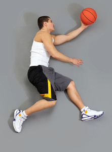 Muscular basketball player catching the ball, overview