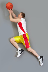 Muscular basketball player slamming the ball, overview