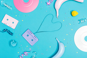 Music flat lay objects with vinyl records and cassette tapes on a blue background