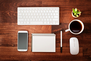 Neat workstation on a wooden desk viewed from overhead with a wireless computer mouse and keyboard, mobile phone, pen, notepad, cup of coffee and houseplant