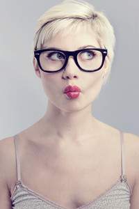 Nerdy and thinking girl with horned glasses. Naturally toned.