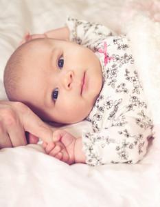 Newborn baby girl grasping her parents finger
