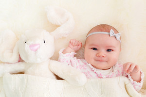 Newborn baby girl laying on her blanket with her stuffed bunny