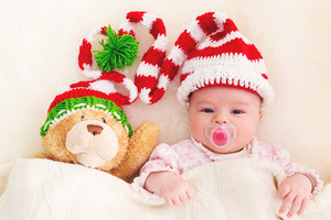 Newborn baby girl laying on her blanket with her teddy bear in a Christmas hat