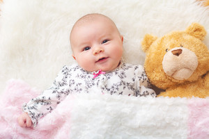 Newborn baby girl laying on her blanket with her teddy bear