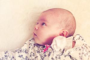 Newborn baby girl laying on her blanket