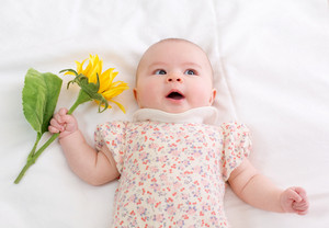 Newborn baby girl lying on her blanket with a sunflower